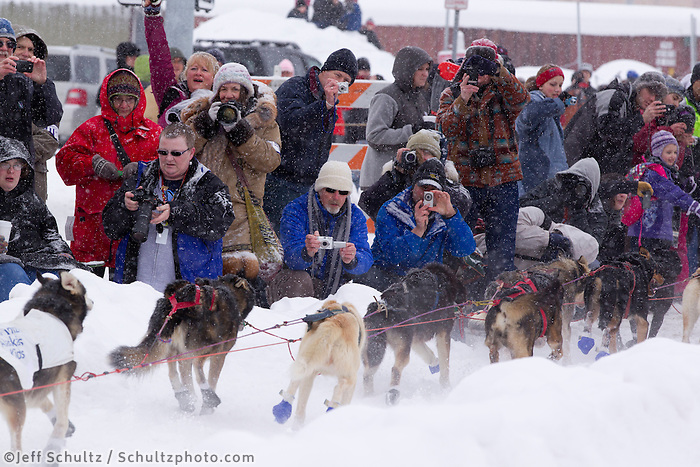 Saturday, March 3, 2012  Spectators take photos of Lance Mackey's team as it passes them by on Cordova street during the Ceremonial Start of Iditarod 2012 in Anchorage, Alaska.