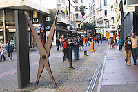 A sculpture of perhaps a pair of scissors by the Uruguay artist Joaquin Torres Garcia outside the entrance to the museum for his work in the city on the pedestrian street Sarandi near Plaza Independencia Independence Square with many people walking. Montevideo, Uruguay, South America