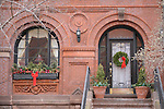 The front of a house in Beacon Hill in Boston, MA with holiday wreaths, bows, and plants.