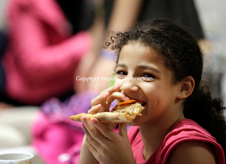 """Prospect, CT- 22 December 2016-122216CM01- Zamiyiah Gordon 8 of Waterbury enjoys a slice of pizza during a Christmas Party for Kelly's Kids at the Cronin Farm in Prospect on Thursday.  The """"old fashioned farm Christmas  party"""" was held by Kelly Cronin, executive director at Kelly's Kids.  The program allows """"children to be children"""" said Cronin.  It also helps them to learn and grow through education and recreation programs.   Christopher Massa Republican-American"""