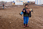 DOMIZ, IRAQ: A young Syrian refugee carries her brother who cannot walk in the deep mud in the Domiz refugee camp in the Kurdish region of northern Iraq...The semi-autonomous region of Iraqi Kurdistan has accepted around 60,000 refugees from war-torn Syria. Around 20,000 refugees live in the Domiz camp which sits 60 km from the Iraq-Syria border...Photo by Younes Mohammad/Metrography