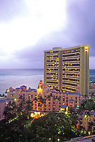 View from above of the Royal Hawaiian Hotel at dusk, with the Sheraton Hotel in the background