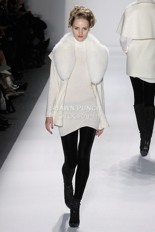 "Model walks runway in an ivory handloomed cashmere/silk ribbed vest w/fox collar, and ivory handlomed cashmere/silk ribbed turtleneck+velvet leggings, from the Zang Toi Fall 2012 ""Glamour At Gstaad"" collection, during Mercedes-Benz Fashion Week New York Fall 2012 at Lincoln Center."