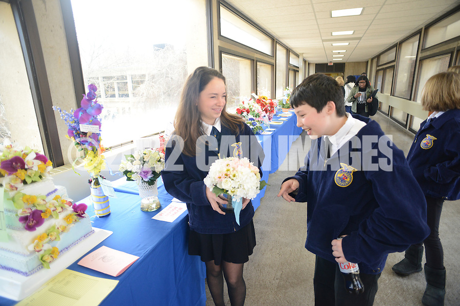 Remy Kwityn (L), 12 a student at Northern Burlington County High School holds her display in the celebration category as she chats with classmate Josh Cassidy, 13, at the Annual New Jersey FFA Floral Design competition, part of the state FFA Horticultural Exposition at Mercer County College Friday, March 13, 2015 in Ewing,  New Jersey. (Photo by William Thomas Cain/Cain Images)