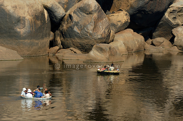 Tourists floating down the Tungabhadra River in traditional nut shell style boats. India, Karnataka, Hampi.