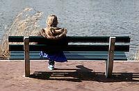 Meisje zit alleen  op een bankje aan het water