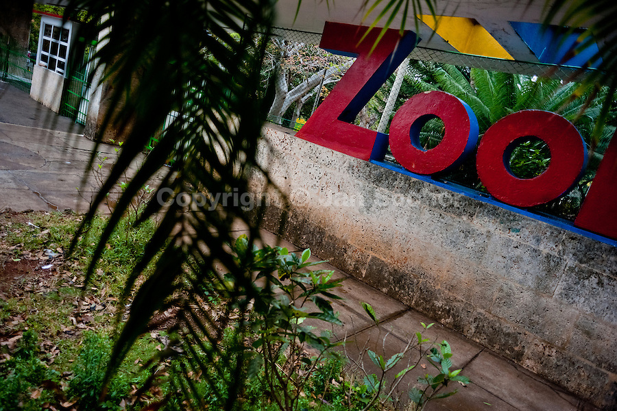 The entrance gate to the Havana Zoo decorated with a large typographic sculpture, Havana, Cuba, 12 February 2011. The largest and the oldest zoo in Cuba (founded in 1939) is located in a centric neighborhood of the capital. Since the 1990s Cuba struggles with chronic economic crisis and therefore the strong marks of rundown and lack of sources are evident within the whole zoological garden. A lot of cages are empty and out of use for long time, the remaining animals are captured in poorly maintained pits. Concrete enclosures have no vegetation, all facilities are unkept. The food supply is often inadequate and visitors throw junkfood to the animals because there are no zookeepers around.