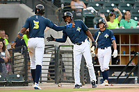 Shervyen Newton (3) of the Columbia Fireflies is greeted by Hansel Moreno after scoring a run in a game against the Rome Braves on Tuesday, June 4, 2019, at Segra Park in Columbia, South Carolina. Columbia won, 3-2. (Tom Priddy/Four Seam Images)