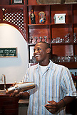 EXUMA, Bahamas. The Bartender mixing a cocktail at the Hill House Bar of the Fowl Cay Resort.