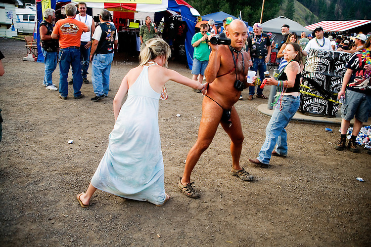 People whip and spank a man wearing little at the Testicle Festival at the Rock Creek Lodge in Clinton, MT.  The Rock Creek Lodge in Clinton, MT, has hosted the annual Testicle Festival since the early 1980s.  The four day festival and party revolves around the consumption of so-called Rocky Mountain Oysters, which are deep-fried bull testicles.