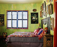 In the bedroom walls of streaked papaya green are an interesting backdrop to a collection of paintings and carvings