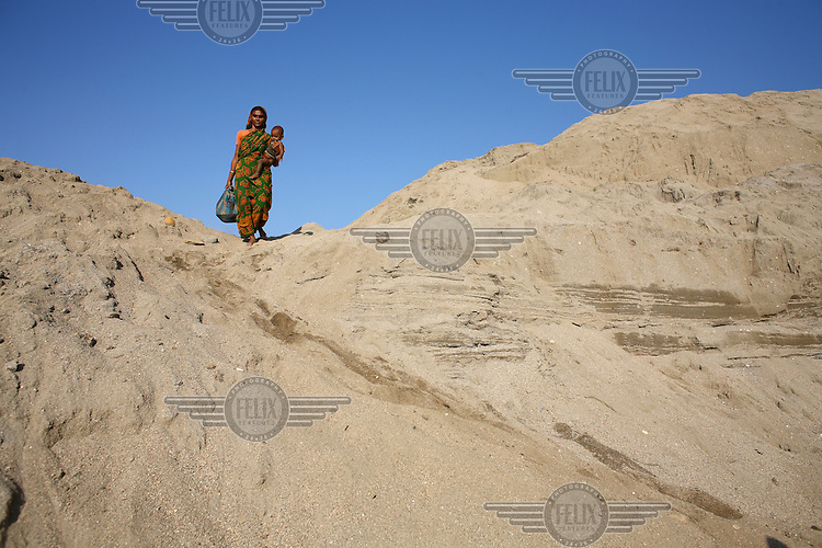 A woman carries her young child with her as she prepares to start work at Bhollar Ghat. At least 10,000 people, including 2,500 women and over 1,000 children, are engaged in stone and sand collection from the Bhollar Ghat on the banks of the Piyain river. Building materials such as stone and sand, and the cement which is made from it, are in short supply in Bangladesh, and commands a high price from building contractors. The average income is around 150 taka (less than 2 USD) a day.