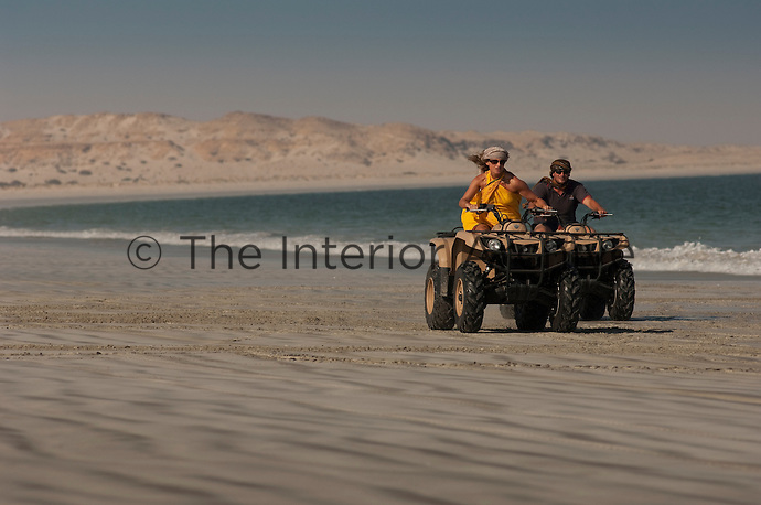 A man and a woman having a race on quad bikes along the beach