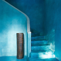 The walls and steps of this simple concrete staircase have been painted a turquoise blue