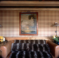 A detail of a country styled sitting room with a beamed ceiling and checked pattern fabric wall covering. A landscape painting is hanging on the wall above a brown leather sofa, which is draped with a fur throw.