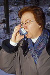 Woman using puffer inhaler for asthma treatment