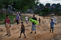A man carries a body of a child for the funeral procession at a camp for Rohingya people in Ukhiya.
