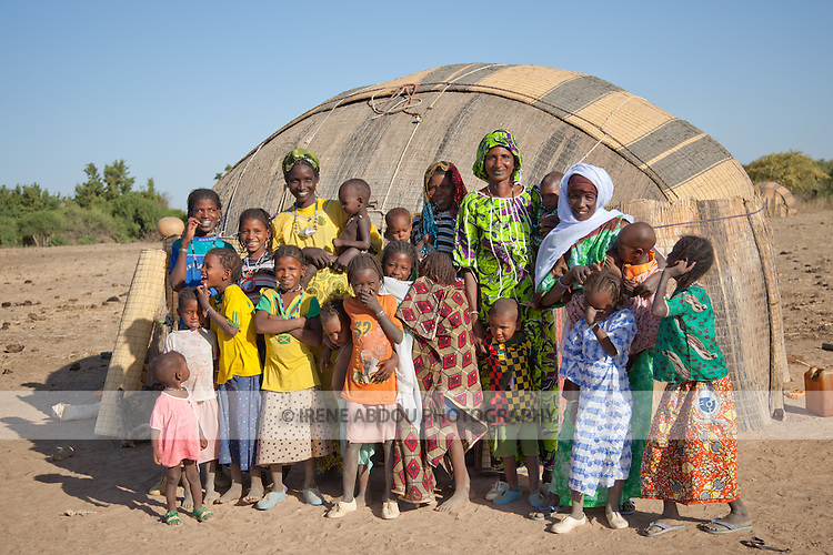 In the seasonal village of Bantagiri in northern Burkina Faso, Fulani women and children stand outside a straw mat house.  The Fulani are traditionally nomadic pastoralists, crisscrossing the Sahel season after season in search of fresh water and green pastures for their cattle and other livestock.  The straw mat house can be reassembled and dissasembled at will.