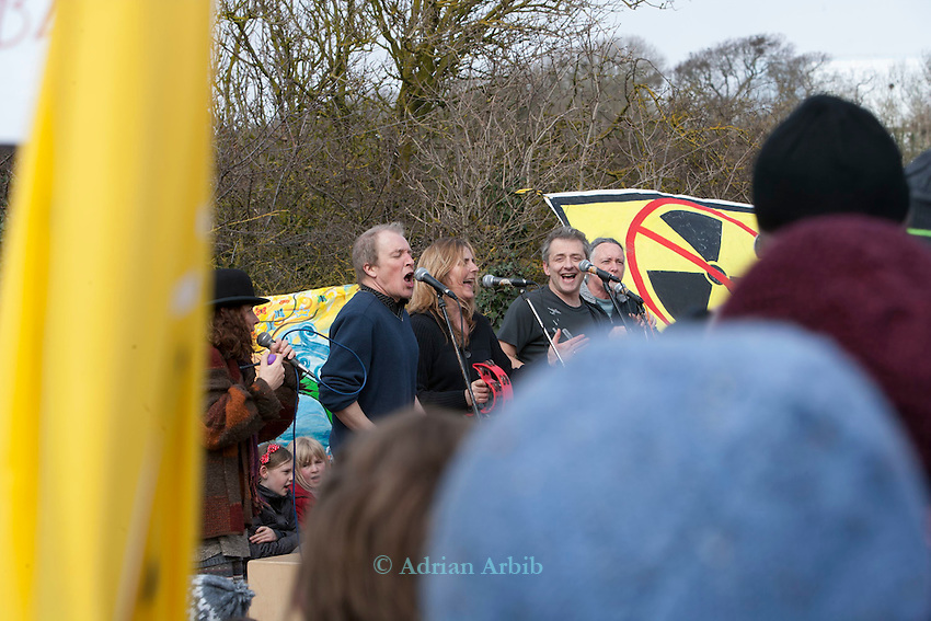 Theo Simon of Sieze the Day  sings protest  songs at the gates of Hinkely c  power station, Somerset ; during   a march against the building of new nuclear in the UK