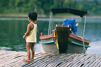 A young boy stands near a longtail boat on a rainy moring in southern Thailand. Floating bamboo bungalows are the only accommodations in remote areas of the Khao Sok National Park. They are owned by Thai families who live and work at the bungalows, often with their entire family.