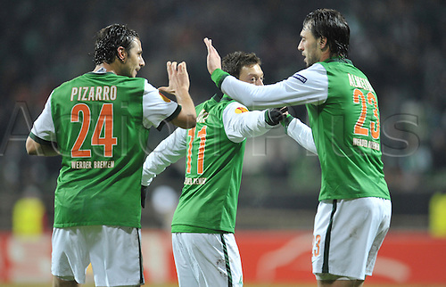 Bremen's Claudio Pizarro (L-R) celebrates his 4-1 score with teammates Mesut Oezil and Hugo Almeida during the Europa League last 32 second leg match Werder Bremen vs Twente Enschede at Weser stadium in Bremen, Germany, 25 February 2010. German Bundesliga club Bremen defeated Dutch side Enschede 4-1 and goes on to the round of the last 16. Photo: Carmen Jaspersen /Actionplus. Editorial Use UK.