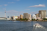 A tourist pleasure boats on the Sumida River with Tokyo Skytree behind. Tokyo, Japan. Friday November 4th 2016