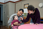 Berkeley CA Adoptive parents (Cuban father) feeding their Guatemalan baby, nine-months-old  MR
