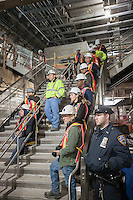 Transit workers watch the news conference at the new 34th Street-Hudson Yards terminal station on the 7 Subway line extension in New York on Friday, December 20, 2013. The new tunnel from Times Square, which will open in the Fall of 2014,  terminates 108 feet below street level at West 34th Street and Eleventh Avenue rat the doorstep of the rezoned 45 block Hudson Yards development. (© Richard B. Levine)