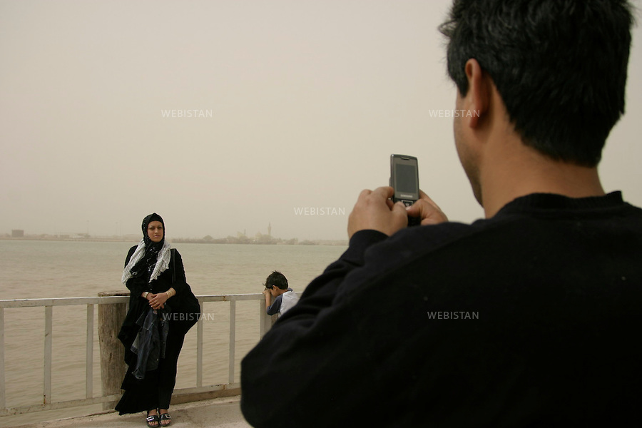 Iran. Khuzistan province. March 22, 2009. Arvand Kenar. A man takes a photo of his wife with his mobile phone in front of Arvandrud river, the natural border between Iran and Irak, and the main territorial dispute at the origin of the Iran-Iraq war (1980-1988). Every year, during the celebration of Nowrooz, the Iranian new year, thousands of Iranians from all over the country, called &quot;Rahian-e Noor&quot; (Caravan of light in Persian), helped by state organizations, gather on former battle fields to commemorate their loved ones who died as soldiers or Basijis. All expenses of this pilgrimage being paid by the State, makes it a favored touristic destination for  families of humble background. The Iran-Iraq War was one of the deadliest armed conflicts of the last quarter of the twentieth century, leaving one million victims.<br />