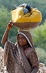 A woman returns from doing her family's laundry in a stream near her home in a village in Pakistan.