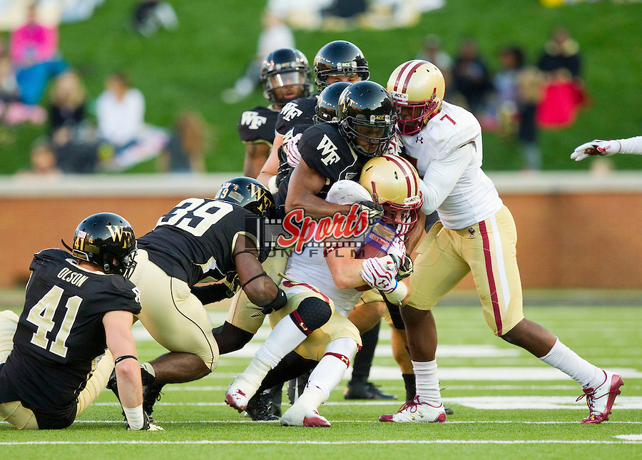 David Dudeck (26) of the Boston College Eagles is wrapped up by Chibuikem Okoro(6) and Justin Jackson (39) of the Wake Forest Demon Deacons at BB&T Field on November 3, 2012 in Winston-Salem, North Carolina.  The Demon Deacons defeated the Eagles 28-14.  (Brian Westerholt/Sports On Film)