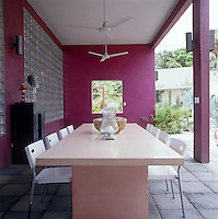 The walls of an outdoor dining room on this covered terrace are painted a bright fuchsia pink creating a vivid contrast with the green of the garden beyond