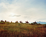 USA, Montana, cowboys and cowgirls riding horses at dawn, Gallatin National Forest, Emigrant