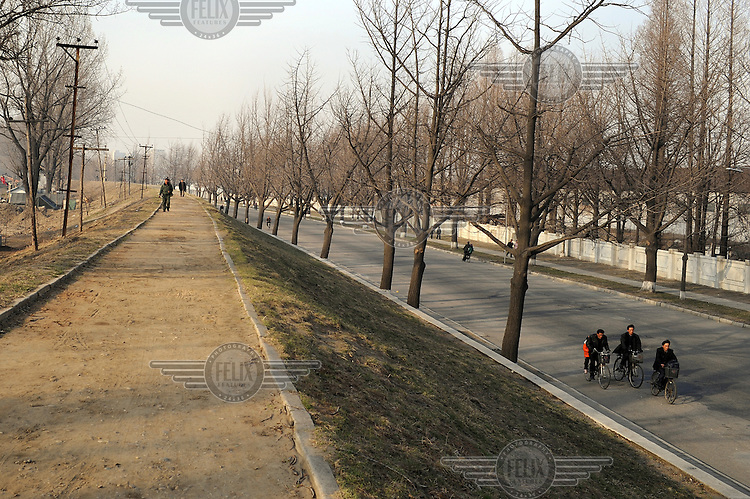 People cycling and walking beside the Taedong River...