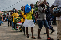 MONROVIA, LIBERIA - AUGUST 23, 2014:   Liberians carry food as they are escorted by Liberian Police and Army personnel, to waiting friends and family, during the fourth day of the government's Ebola quarantine on the neighborhood of West Point  on August 23, 2014 in Monrovia, Liberia. <br /> photo by Daniel Berehulak