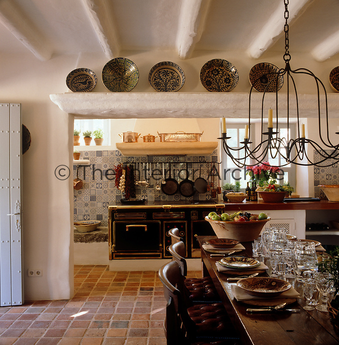Local ceramic plates are displayed above the entrance that separates the kitchen from the dining area
