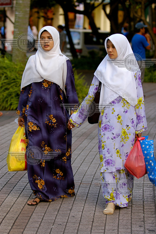 Women wearing Muslim headscarves out shopping on Jalan Tunku Abdul Rahman downtown.