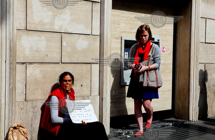 A woman, begging besides an ATM, holds a sign that reads: 'Please help me. I have no money for a nose prosthesis. I have four children and have no money. Many thanks'.