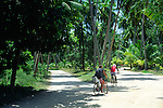 People cycling along sandy road on the island of La Digue, Seychelles
