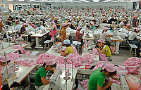 Young female workers on production lines in a textile factory in Yixing city, in the Jiangsu Special Development Zone that makes clothes for western companies including Umbro Sports and New Balance. Much of the world's textile manufacture has moved to China due to relatively low labor rates and high productivity and those clothes are almost exclusively made by women between 6 and 25 years old..23 Sep 2006