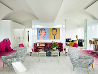 The luxurious penthouse apartment is full of edgy chic and sizzling colour. In the living room a pair of silk-screened prints by Andy Warhol hang above a 1960s Edward Wormley sofa upholstered in a Scalamandré velvet. The chairs in the foreground are by Charles Ramos, and the side table is by Achille Salvagni; the Louis XVI stools, circa 1780, are from Bernd Goeckler Antiques, the Lucite barstools are from the 1970s, and the bear sculpture is by Paola Pivi.