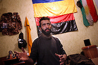 "UKRAINE, 02.2016, Novohrodivka, Oblast Donetsk. Ukrainian-Russian conflict concerning Eastern Ukraine / Foreign volunteers (""Task Force Pluto"") fighting with the far-right militia Pravyi Sektor against the Russian-backed separatists: Ben (Austria) gestures in his room, the wall behind him is full of memorabilia like the jacket of a fallen comrade, an Ukrainian flag, a Peshmerga flag from Iraq and a Right Sector flag (red-black) with a swastika on it. © Timo Vogt/EST&OST"
