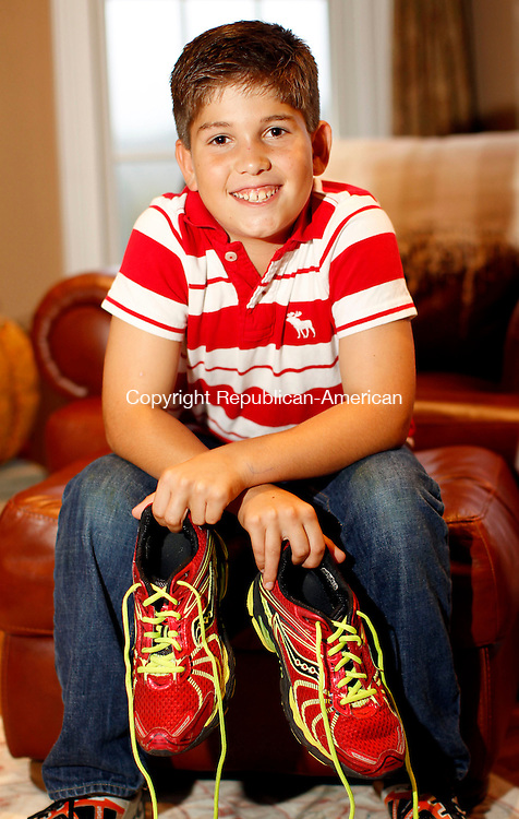 Southbury, CT-03 October 2012-100312CM06-  Justin Ordway, 10, of Southbury poses for a photograph with his running shoes Wednesday afternoon in Southbury.  Ordway, who was diagnosed with a rare white blood cell disorder at the age of 7, has been treated, which has appeared to have worked as he has been in complete remission.  Ordway was selected by the Hartford Marathon Foundation to run in the 5k portion of this years ING Hartford Marathon, as part of the 2012 Elite Inspiration Team.   Christopher Massa Republican-American
