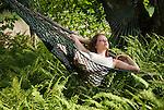 Woman lying in hammock above ferns