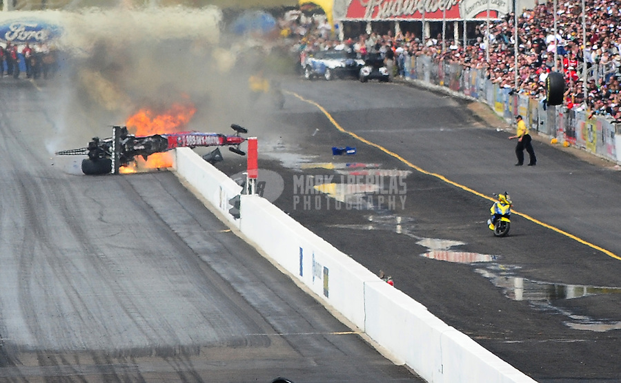 Feb. 21, 2010; Chandler, AZ, USA; NHRA top fuel dragster driver Antron Brown bursts into flames as he crashes during the Arizona Nationals at Firebird International Raceway. A tire from his car (right) flew over the trackside wall and into a spectator area causing serious injuries. Mandatory Credit: Mark J. Rebilas-