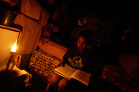 Brook's brother, Mathias 7, reads a school book before dinner in  the shack where he lives in the center of Addis Ababa, Ethiopia on Wednesday June 06 2007.