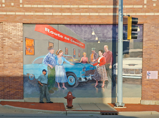 "A Paserby leans against a Route 66 Mural on the side of a auto repair shop depicts the former ""Mother Road"" that went through town, Joliet, IL"
