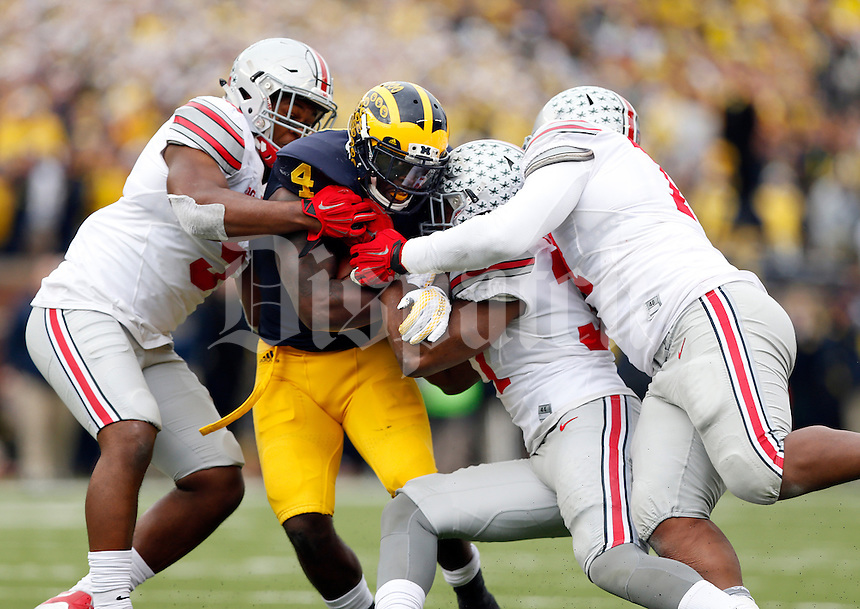 Michigan Wolverines running back De'Veon Smith (4) runs through Ohio State Buckeyes linebacker Raekwon McMillan (5), linebacker Joshua Perry (37) and defensive lineman Michael Hill (77) during the second quarter of the NCAA football game in Ann Arbor on Nov. 28, 2015. (Adam Cairns / The Columbus Dispatch)