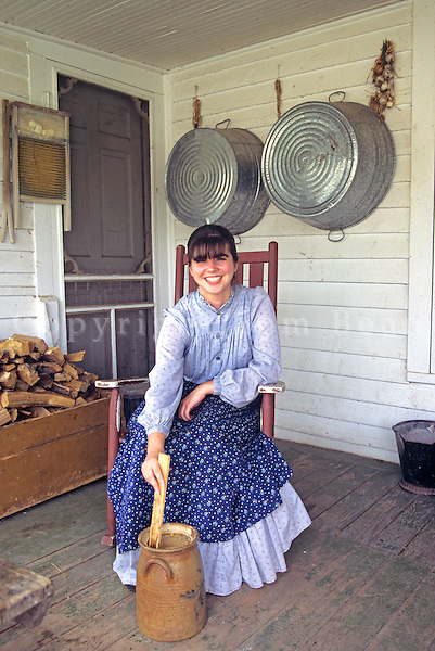 Young woman demonstrates soap making while sitting on porch of 1900  era farm house at Living History Farms, Des Moines, Iowa, AGPix_0502..