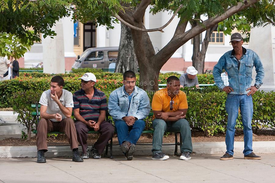 Cuba, Cienfuegos.  Five Men Resting in the park, the Parque Marti.